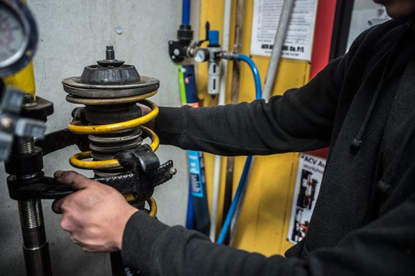mechanic fixing car spring suspension