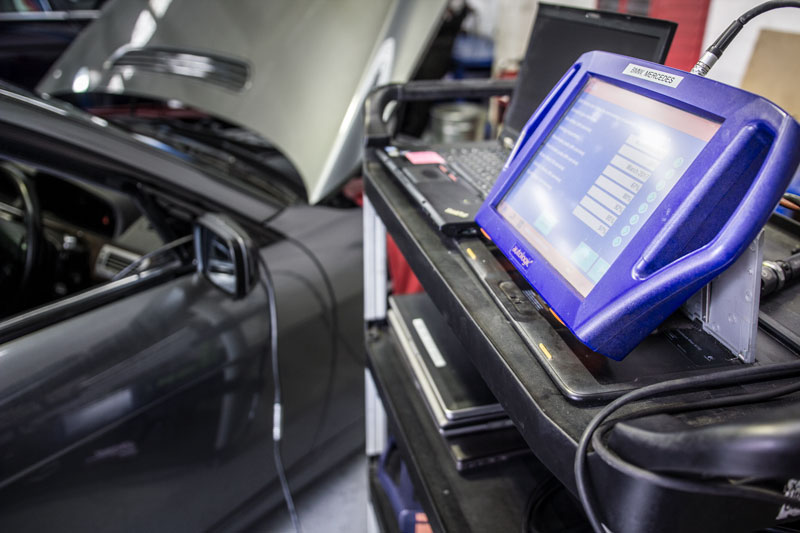 diagnostic tool sitting on tool shelf next to vehicle being diagnosed