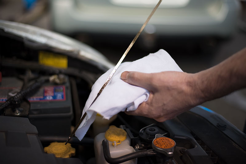 Mechanic cleaning dipstick after checking oil
